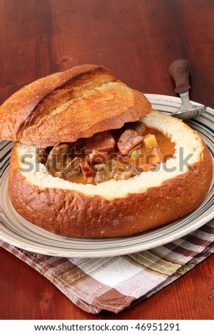 Goulash soup with beef, potato and meat sausage, served in a bread bowl - stock photo
