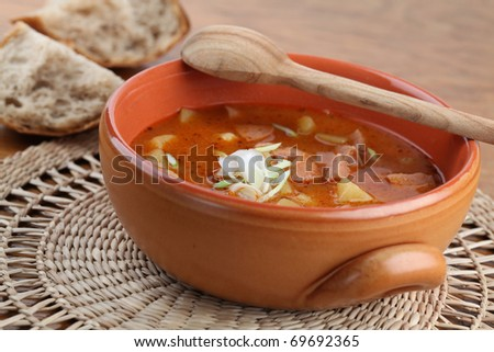 Goulash soup with meat sausage and potatoes garnished with spring onion in a brown bowl. Shallow dof