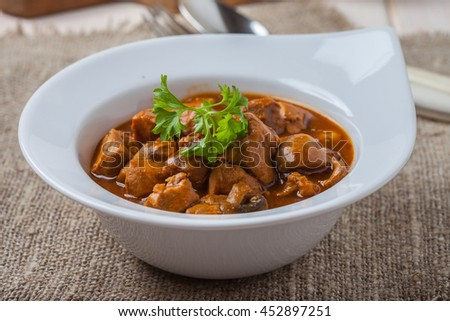 Goulash soup with pork and mushrooms on wooden table.