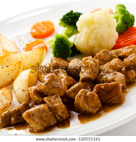 Goulash with roasted potatoes and vegetables - stock photo