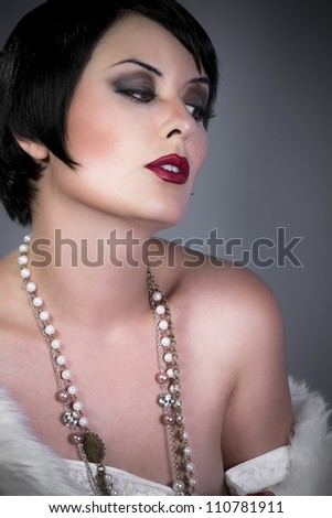 gourgeos female brunette flapper wearing pearls necklace and fur - stock photo