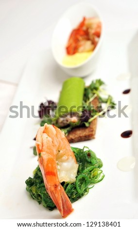 Gourmet appetizer, starter or Entree of a french dish with seafood mixed among salad leaves.
