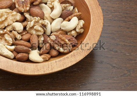 Gourmet Assorted Nuts on a wooden bowl - stock photo