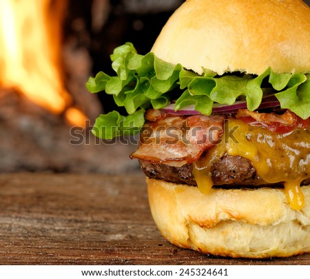 Gourmet bacon cheeseburger with lettuce and tomato in front of the fire - stock photo