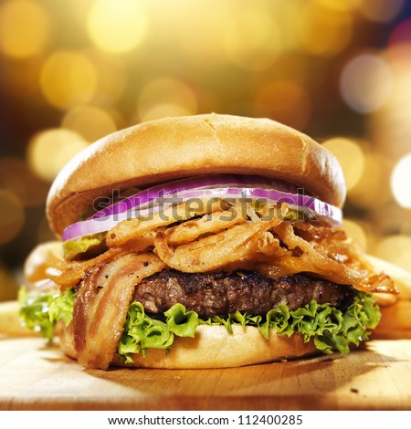 gourmet bacon hamburger with golden background and copy space composition. - stock photo