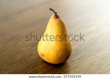 Gourmet bosc baking pear against wood - stock photo