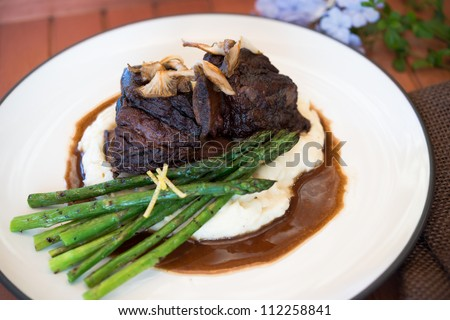 Gourmet braised short ribs sitting atop mashed potatoes with asparagus and sauce - stock photo