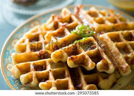 Gourmet breakfast and brunch setting with savory waffles and pancakes topped with fresh fruit puree reduction on fancy plates - stock photo