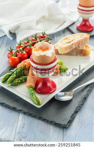 Gourmet breakfast with soft boiled egg, green asparagus and smocked salmon - stock photo