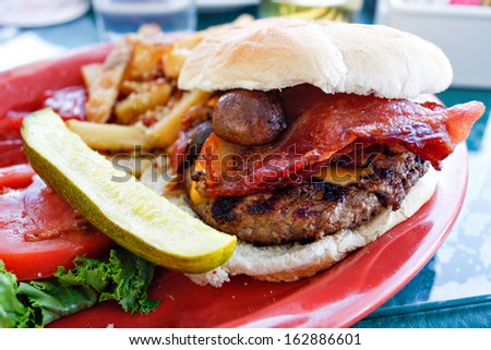 Gourmet burger with cheese mushrooms and thick cut bacon and a side of a pickle and some parmesan french fries. - stock photo