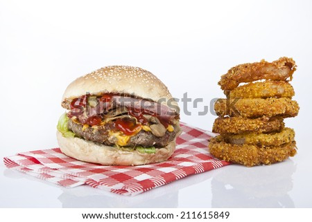Gourmet burger with cheese mushrooms and thick cut bacon and a side of a pickle and some parmesan french fries, onion fries. - stock photo