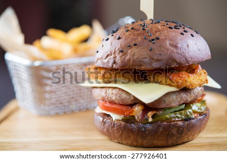 gourmet burger with fries on wooden table and black background - stock photo