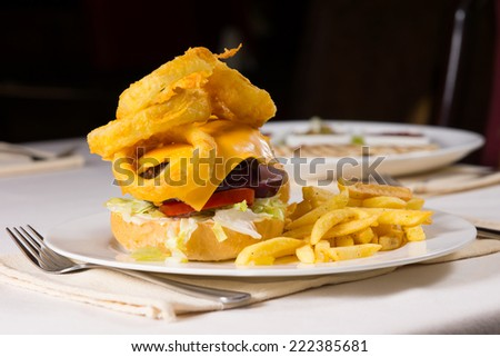 Gourmet Cheeseburger and French Fries on Plate at Place Setting on Restaurant Table - stock photo