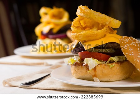 Gourmet Cheeseburgers Piled High with Toppings Served on Plate on Restaurant Table - stock photo