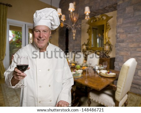 Gourmet Chef toasting with a glass of wine with holiday dining table in background - stock photo