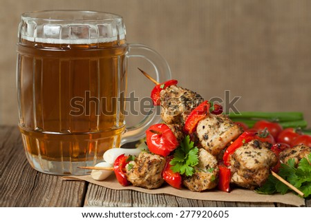 Gourmet chiken kebab skewer barbecue meat on bamboo sticks with glass of beer on rustic wooden table background. Rustic style, natural light. - stock photo