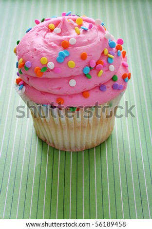 gourmet cupcake on green background vertical - stock photo