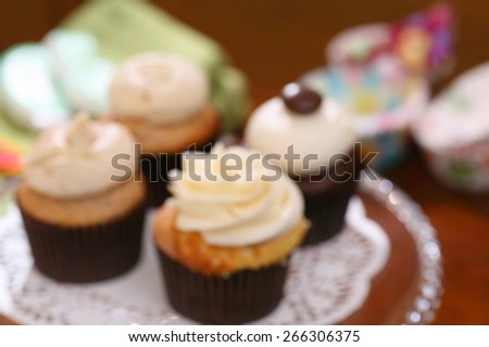 Gourmet cupcakes baked and frosted with icing vanilla and intentionally blurred for background use - stock photo