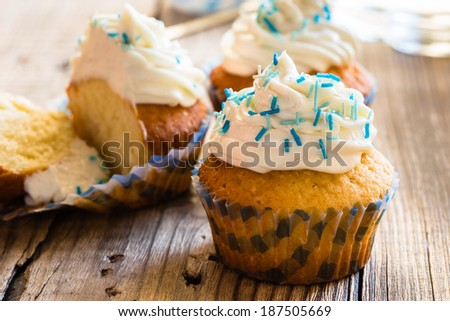 Gourmet cupcakes with white buttercream frosting and sprinkles on wooden background - stock photo
