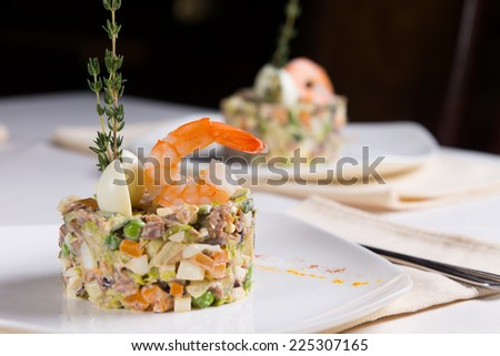 Gourmet Delicious Main Dish Recipe. Combination of Sea Food and Vegetables on White Plate. Served on the Table at the Restaurant. - stock photo