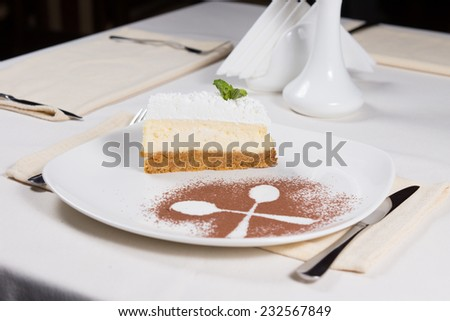 Gourmet Delicious Three Layered Cake with Spoon Outline Using Cocoa Powder on White Plate. Dine in White Table at the Restaurant. - stock photo