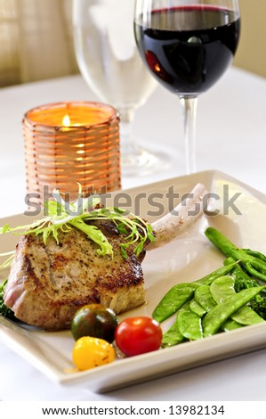 Gourmet dinner of veal rib chop and vegetables - stock photo