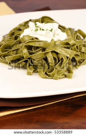 Gourmet exquisite spinach fettuccine alfredo pasta on fancy dinner table - stock photo