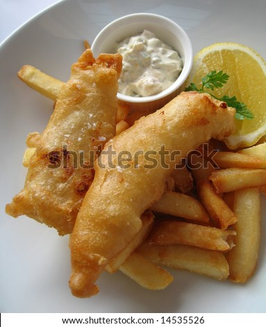 Gourmet fish and chips with a slice of lemon and tartar sauce. - stock photo
