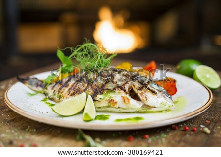Gourmet fish - delicious grilled golden sea bream with vegetable garnish served on a wooden table, fireplace on background - stock photo