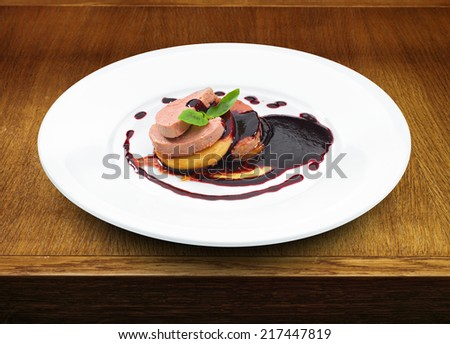Gourmet foie gras served with red berry sauce and decorated with basil leaf. Wooden table - stock photo