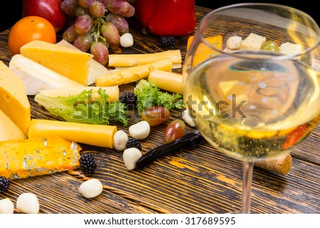 Gourmet Food Still Life - Close Up of Glass of White Wine Amongst Variety of Cheeses and Fresh Fruit on Rustic Wooden Table - stock photo