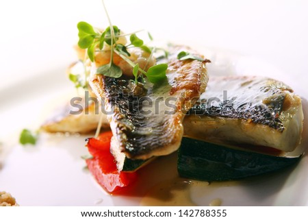 Gourmet grilled fish served with prawns and garnish - stock photo