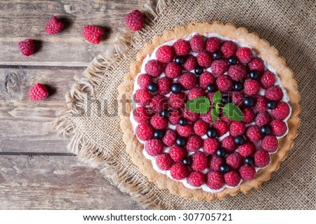 Gourmet homemade raspberry tart pie. Traditional cake with raspberries, blackberry and whipped cream on vintage wooden background. Rustic style and natural light - stock photo