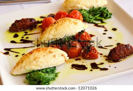 Gourmet Italian Gnocchi, with roasted tomatoes and arugula. - stock photo