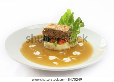 Gourmet meatloaf on a bed of vegetables and mash garnished with trimmed lettuce - stock photo