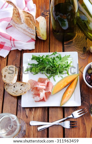 Gourmet platter of prosciutto, rocket and cantaloupe with bread and wine  - stock photo