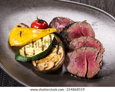 Gourmet portion of rare roast beef fillet garnished with grilled vegetables on dark background - stock photo