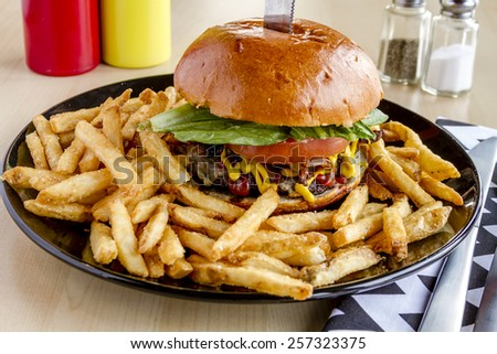 Gourmet pub hamburger with bacon sitting on black plate with french fries - stock photo