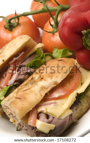 gourmet roast beef sandwich havarti cheese lettuce tomato red onion remoulade dressing on rustic rosemary bread - stock photo