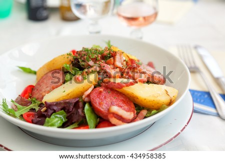 Gourmet salad with vegetables and fried ham served in a small beach restaurant in Cannes, France