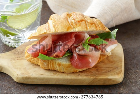 gourmet sandwich croissant with ham and  basil - stock photo