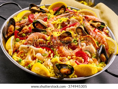 Gourmet seafood paella with pink marine prawns and mussels on yellow saffron rice with peas and bell peppers, close up view in a rustic metal dish