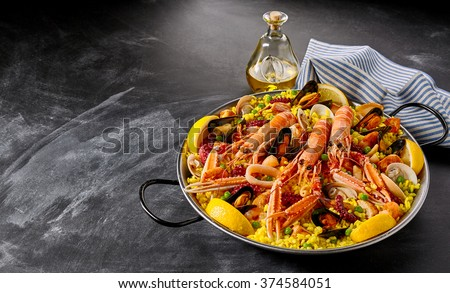 Gourmet seafood Valencia paella with fresh langoustine, clams, mussels and squid on savory saffron rice with peas and lemon slices, close up view