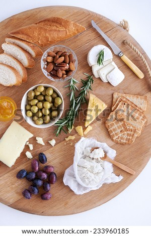 Gourmet selection of cheeses, cheddar fresh ricotta gouda brie goat cheese, with nuts olives grapes crackers and bread, served on a large wooden board - stock photo
