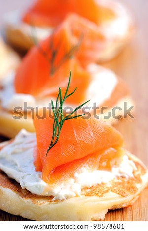 Gourmet smoked salmon and cream cheese blinis on a wooden platter - stock photo
