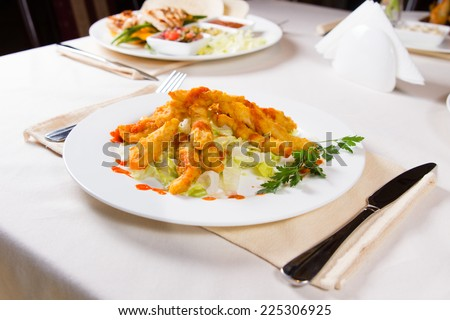 Gourmet Tasty Fried Fish Meat with Herbs and Vegetables on White Round Plate Served on the Table. - stock photo