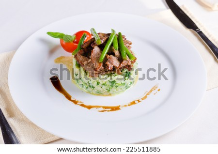 Gourmet Tasty Well- Cooked Beef Meat and Green Beans on Risotto Main Dish. Prepared on White Round Plate with Utensils on Sides. - stock photo