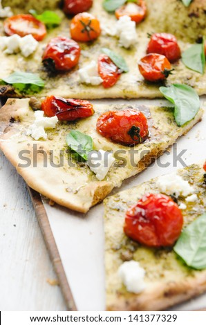 Gourmet thin crust pizza with roasted tomatoes, fresh basil and feta cheese - stock photo