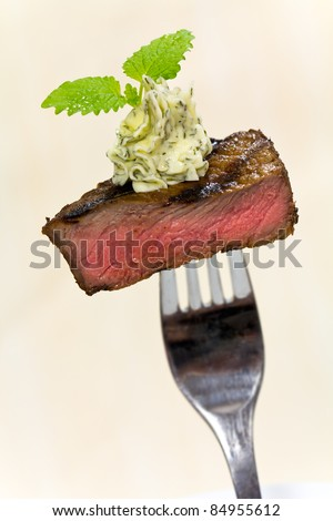 Gourmet Time,piece of a grilled steak with herb butter on a fork - stock photo