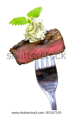 Gourmet Time,piece of a grilled steak with herb butter on a fork,isolated on white